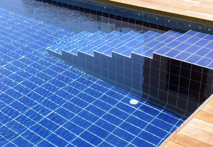 rectangular pool tiles placed vertically on pool bottom while horizontally on pool step.jpg