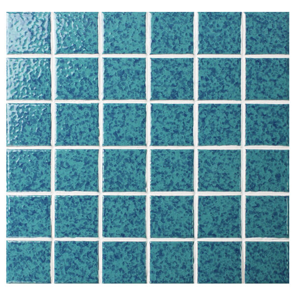 cut turquoise pool tile sheet to have chips and decorate pool step.jpg